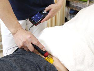 えぐち鍼灸整骨院で腰痛の患者様にハイボルテージを施術している様子