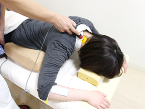 手や首に痺れがあり、ハイボルテージを施術している様子